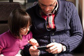 Image of child and father with phone courtesy of Shutterstock