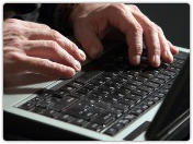 Man hands on computer. Image courtesy of Shutterstock
